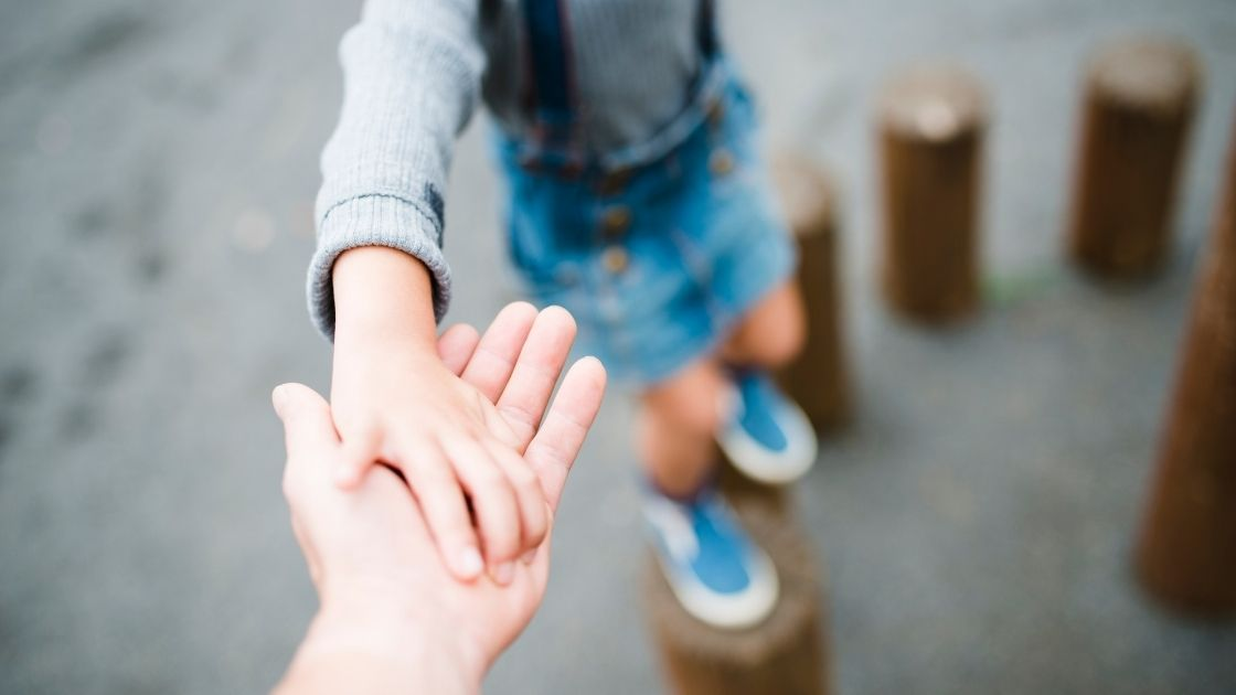 child holding parent hand